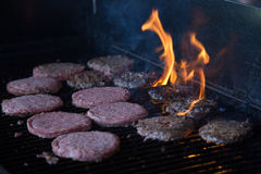 Hamburgers on Grill with Flames Royalty Free Stock Photos