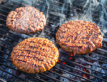 Hamburgers on the grill royalty free stock images