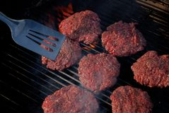 Hamburgers on the Grill with Spatula Royalty Free Stock Images