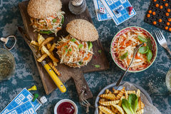 Hamburgers with grilled chicken and cole slaw on a wooden board on the table with cards and bingo chips, top view. royalty free stock images