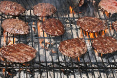 Hamburgers Grilling Over Flames Royalty Free Stock Photos