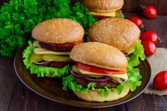 Hamburgers at home (bun, tomato, cucumber, onion rings, lettuce, pork chops, cheese) in a clay bowl. On a wooden background. Close-up Royalty Free Stock Photography