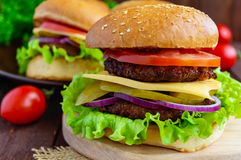 Hamburgers at home (bun, tomato, cucumber, onion rings, lettuce, pork chops, cheese). In a clay bowl on a wooden background. Close-up Stock Photo