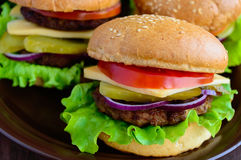 Hamburgers at home (bun, tomato, cucumber, onion rings, lettuce, pork chops, cheese). In a clay bowl on a wooden background. Close-up Stock Images