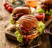 Hamburgers, homemade burgers with grilled buns with addition of addition of beef cutlet, lettuce, tomato,pickled cucumber, grille stock photos