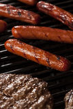 Hamburgers and Hot Dogs on the Grill Royalty Free Stock Images