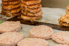Hamburgers and hotdogs cooking Stock Images