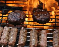 Hamburgers and meat on the grill Stock Image