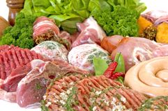 Hamburgers and other fresh meat. Variety of fresh meat garnished with lettuce and parsley, studio shot Royalty Free Stock Photo