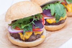 Hamburgers pepper cheese onions sauce tomatoes on paper Stock Photography