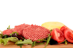 Hamburgers, salade de tomates Image stock