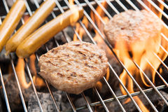 Hamburgers and sausages cooking over flames on grill. Royalty Free Stock Photo