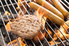 Hamburgers and sausages cooking over flames on grill. Royalty Free Stock Images