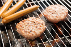 Hamburgers and sausages cooking over flames on grill Royalty Free Stock Photos