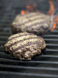 Hamburgers sizzling on the grill. With flames Stock Image