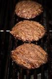 Hamburgers sur le gril Photographie stock libre de droits