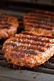 Hamburgers sur un gril Photographie stock libre de droits