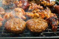 Hamburgers sur un gril Photographie stock