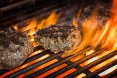 Hamburgers sur un gril flamboyant Images libres de droits