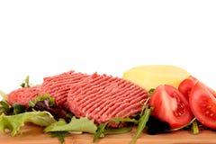 Hamburgers, tomatensalade Stock Afbeelding