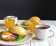 Hamburgersandwich, kop thee en jus d'orange voor ontbijt Stock Fotografie