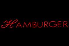 Hamburgeru neonowy znak na czerni Fotografia Royalty Free
