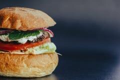 Hamburgervlieger Kaashamburger met geroosterde vlees, kaas, salade en uiringen Close-up van heerlijk vers huis gemaakt tot hambur royalty-vrije stock afbeeldingen