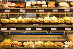 Hamburgery, donuts i kanapki w piekarni szkła kontuarze, Obrazy Royalty Free