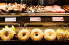 Hamburgery, donuts i kanapki w piekarni szkła kontuarze, Zdjęcia Stock