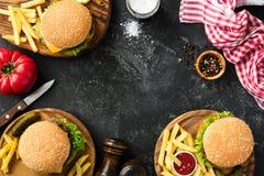 Hamburgery i francuscy dłoniaki na zmroku drylują tło, odgórny widok obrazy stock