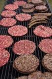 Hamburgery i kiełbasy na grillu Obraz Stock