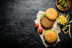 Hamburgery na papierze z Francuskimi d?oniakami, zalewami i pomidorami, zdjęcia royalty free