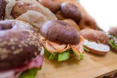 Hamburgery z ryba na drewnianej desce na chlebowym tle Zdjęcie Stock