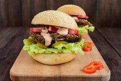 Hamburgery z wątrobowym cutlet, pomidorami, zalewami, sałatą, korzennym kumberlandem i miękką babeczką z sezamowymi ziarnami na t zdjęcia royalty free