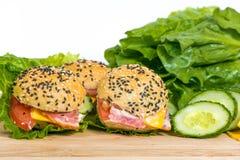 Hamburgery z warzywami i bekonem na drewnianym biurku Zdjęcia Royalty Free