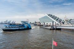 Hamburgo, Alemania - 12 de abril de 2014: Visión en el embarcadero del Dockland y el transbordador que cruza en el buen tiempo en foto de archivo libre de regalías