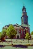 HAMBURGO, ALEMANIA - 8 DE JUNIO DE 2015: Santo Michaels fuera de la iglesia con una alta torre y un reloj en el top, gente exteri Foto de archivo