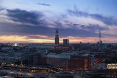 Hamburgo en la puesta del sol - los transbordadores ruedan, iglesia del ` s de San Miguel y torre de la televisión foto de archivo