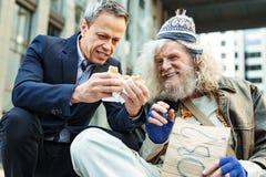 Hamburguer antropófago idoso desabrigado de sorriso do desconhecido fotos de stock