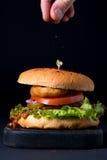 Hamburguer caseiro da galinha em servir a placa de madeira e o man& escuros x27; dedos de s que polvilham a pimenta vermelha Fotos de Stock