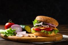 Hamburguer caseiro ou Hamburger do queijo com presunto, tomates, queijo e alface na placa de madeira Copie o espa?o Fast food par imagens de stock