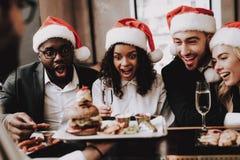 Hamburguer Chapéu do `s de Santa Meninas e indivíduos Homem e mulheres felizes fotos de stock