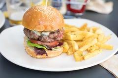 Hamburguer com batatas fritas no restaurante Imagem de Stock Royalty Free