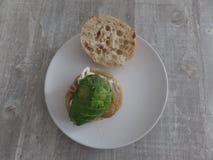 Hamburguer com cebolas e abacate em um rolo do ciabatta foto de stock royalty free