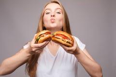 Hamburguer cortante da menina com fome hamburguer com galinha e salada imagem de stock