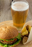 Hamburguer, cunhas roasted da batata e vidro da cerveja imagens de stock