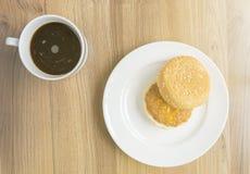 Hamburguer da xícara de café e da carne de porco na tabela de madeira com luz solar Imagem de Stock