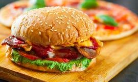 Hamburguer do queijo do bacon com a cebola e a pizza do tomate do rissol de carne com mozzarella, presunto, tomates, salame, pime Imagem de Stock