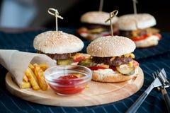 Hamburguer, Hamburger com batatas fritas, ketchup, mostarda e legumes frescos em uma placa de madeira do corte Fotos de Stock Royalty Free