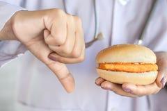 Hamburguer insalubre do fast food da terra arrendada da mão do doutor imagem de stock royalty free